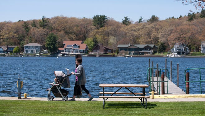 """Katie Bourgois pushes her son Ben in a stroller while walking along Pentwater Lake on Thursday, May 19, 2016 at the Pentwater Municipal Marina in Pentwater, Mich. Bourgois, who recently moved from Lansing, is living in Pentwater temporarily until her family's home in Rockford is ready to move into. """"We love it here, how relaxing it is,"""" Bourgois said. Pentwater, with a population of under a 1,000 people, is home to Mears State Park."""