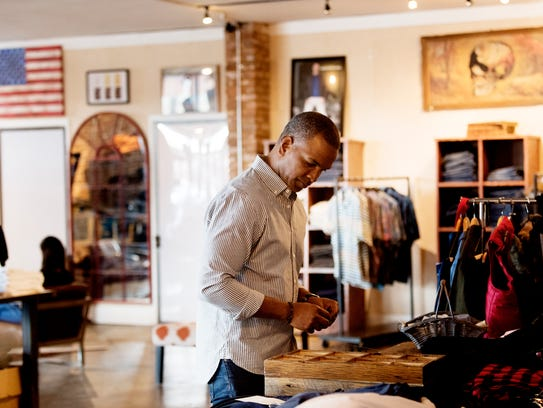 Marcus Hall arranges a display table at his store on