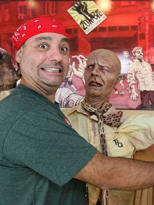 George Formaro, owner of Zombie Burger + Drink Lab clowns, around with a zombie.