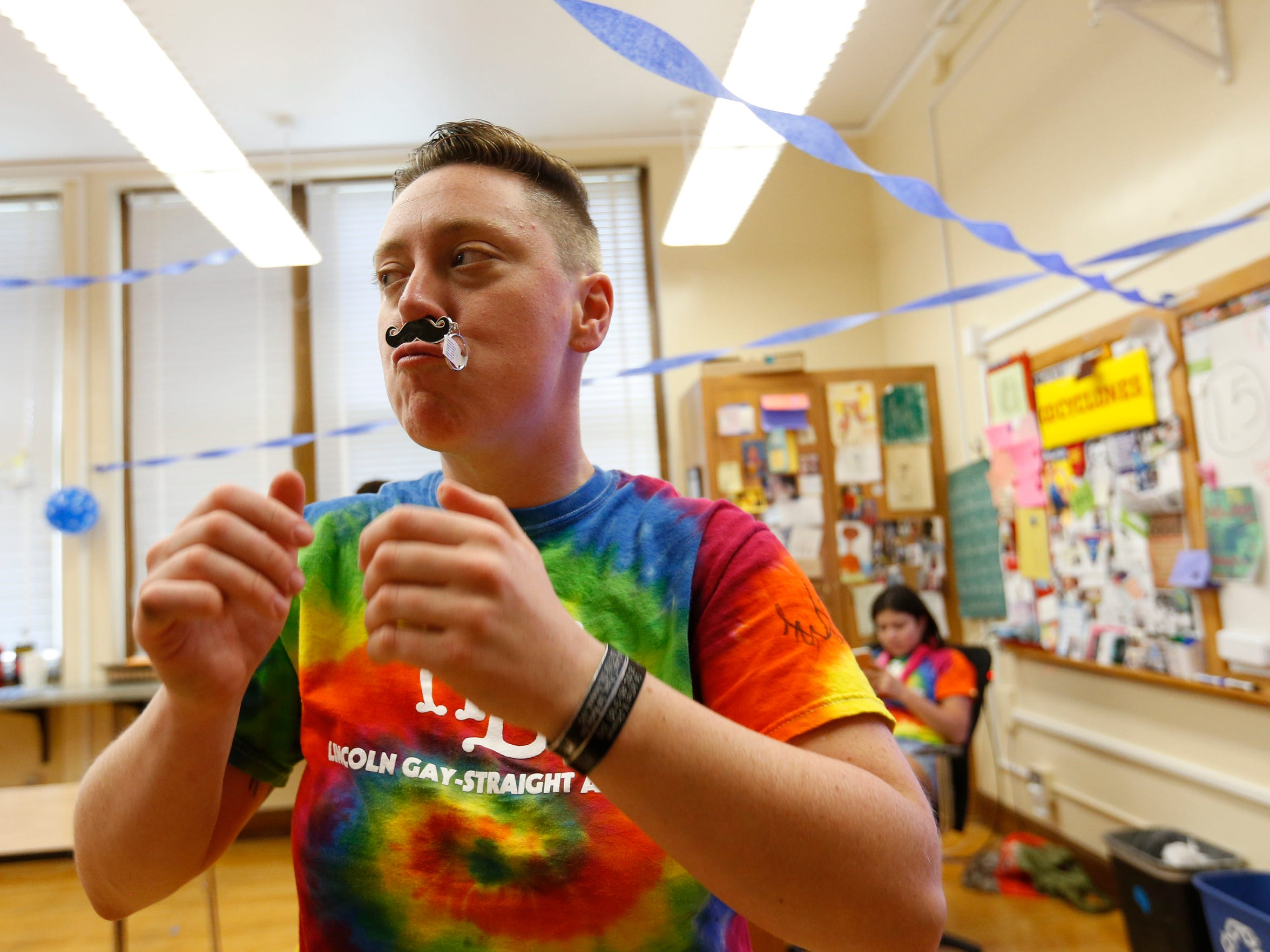 """Jack Schuler balances a mustache keychain under his nose Friday, May 20, 2016, as he arrives at an after school """"It's a Boy"""" party in his honor at Lincoln High School in Des Moines."""