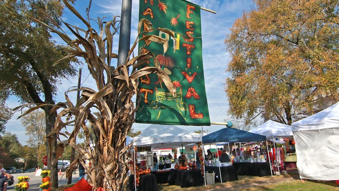Visitors wander around booths of crafts and food during last year's Pendleton Fall Harvest Festival on the Village Green. This year's festival will be Oct. 14 on the green. Any volunteers interested in helping town officials stage the event should call 864-646-9409.