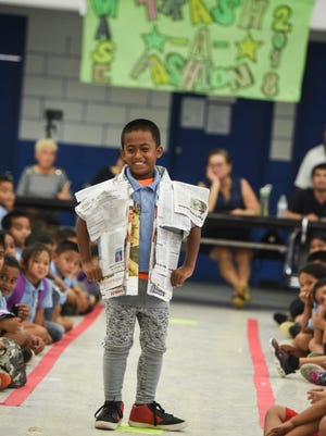 """Student Jfonik Matua, strikes a confident pose in his shirt made with recycled newspapers, during the 4th annual Trash-A-Fashion event at Marcial A. Sablan Elementary School in Agat on Friday, April 20, 2018. The theme for this year's show """"Recycling - It's Worth It"""" and is aimed to raise awareness, change people's attitude and behaviors that will contribute to a healthier Earth."""