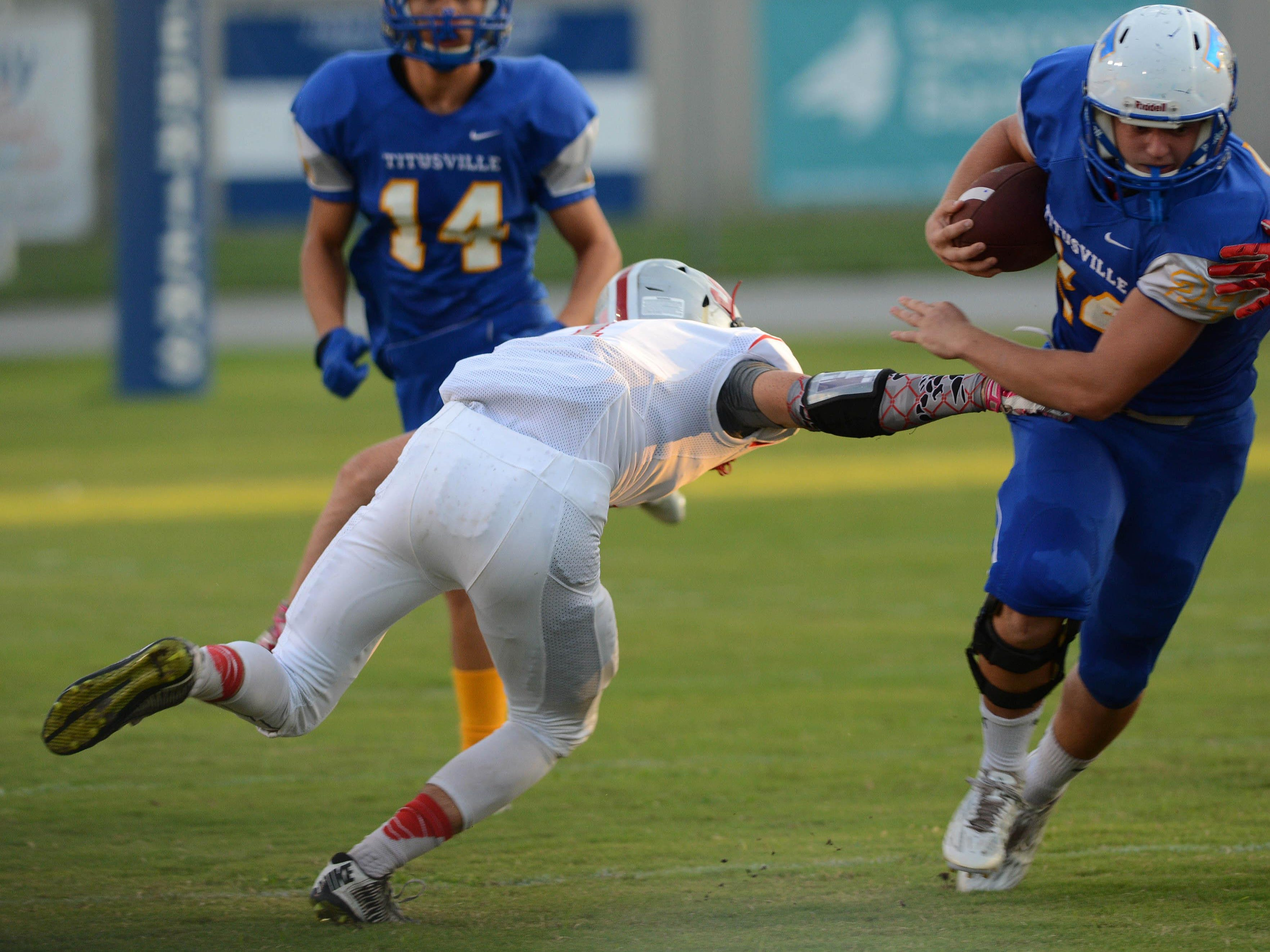 Titusville's Jacob Farris (24) avoids the tackle of Satellite's Alex Nicks during Friday's game in Titusville.