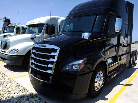 A new Freightliner Cascadia is parked with other large
