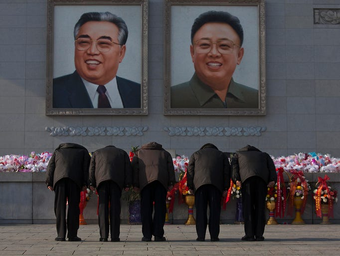 People bow to portraits of the late North Korean leaders Kim Jong Il and Kim Il Sung on Dec. 17 in Pyongyang. It is the second anniversary of the death of Kim Jong Il.