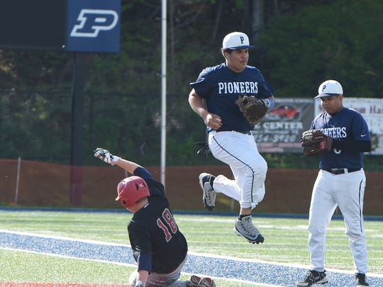 Poughkeepsie's Jesus Fabian Peralta, right, watches as teammate Steven Disla, center, hops over Red Hook's Kevin Jordan, left, after successfully making the tag during Monday's game.