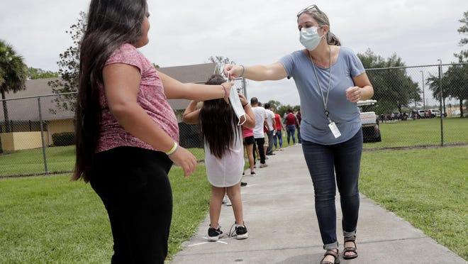 Gretel Cacerces, right, passes out masks to those standing in line for COVID-19 testing at the Florida Department of Health in Collier County on June 7 amid the coronavirus pandemic in Immokalee.