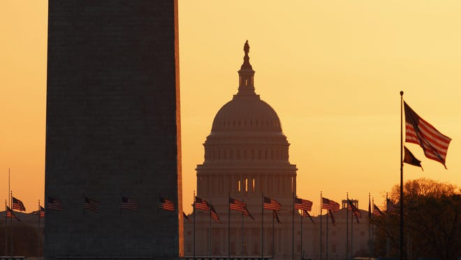 The Washington Monument and the U.S. Capitol are seen in Washington, at sunrise Wednesday, March 18, 2020. The White House has sent Congress an emergency $46 billion spending request for coronavirus-related funding this year.