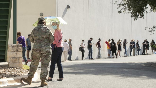 Elsa Demedo, left, and Jeanette Breedlove wait in a lengthy line Tuesday at an early voting location at Ben Hur Shrine Temple in North Austin.