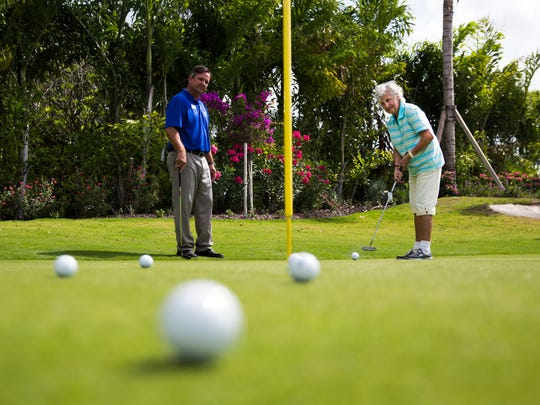 Shirley Harmann, 87, practices her putting with Stan Geer, the community's golf pro, on Wednesday, April 19, 2017 at Vi at Bentley Village in North Naples. Harmann plays every week and is chairperson of the Nine-Hole Club at her senior community.