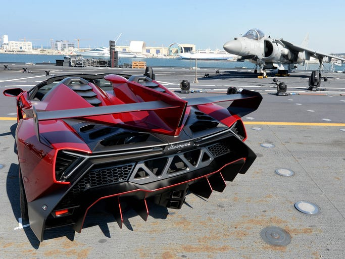 Lamborghini's Veneno supercar stands out against a fighter jet on the deck of an Italian aircraft carrier docked in Abu Dhabi
