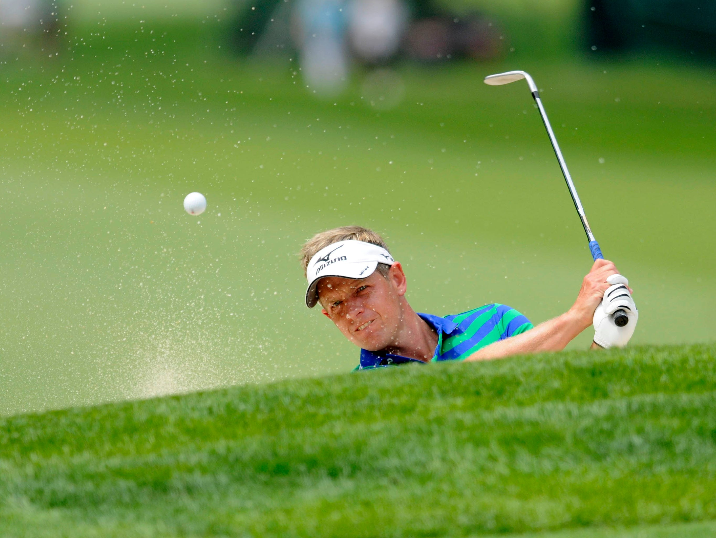 Luke Donald  plays from a bunker on the 2nd green during the practice round of the 95th PGA Championship at Oak Hill Country Club.