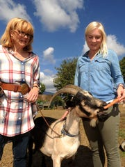 Donna Johanson, left, who co-owns Chivas Skin Care with her daughter Lauren Johanson Jones, watches as Lauren feeds a carrot to Lolly as they pose for a photo at their farm in Fillmore  on Monday. The pair make soap out of goat milk and will be part of the Ventura County Farm Day Tour on Saturday.