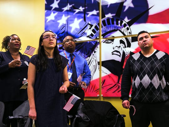 December 14, 2016 - From left to right - Linda Gates, Derek Peeples, Natalia Ramos and her father, Antonio, watch a video during a naturalization ceremony at the Memphis Field Office of the United States Citizenship and Immigration Services at 80 Monroe Ave. on Wednesday. Eleven people, including Dulce Ramos - the mother and wife of Natalia and Antonio Ramos - became U.S. citizens during the ceremony. USCIS also had a ribbon cutting event to celebrate its new Memphis office in the Brinkley Plaza Building. USCIS oversees the legal immigration system in the country.