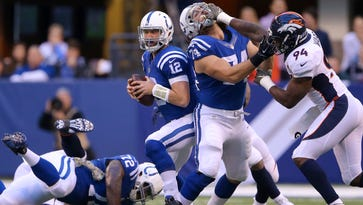 Indianapolis Colts quarterback Andrew Luck (12) is forced out of the backfield as tackle Anthony Castonzo (74) battles Denver Broncos outside linebacker DeMarcus Ware (94) during the first half of an NFL football game Sunday, Nov. 8, 2015, at Lucas Oil Stadium.