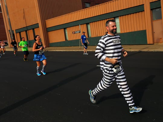Eric Marcotte, of Paris, Kentucky, races in prison stripes during the Shawshank Hustle on Saturday morning.