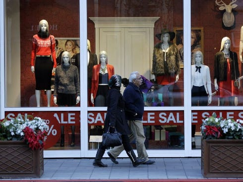 Shoppers walk in front of a store advertising a sale on Dec. 9, 2013, in San Jose.