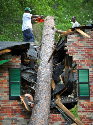In this photo taken Monday, April 27, 2015, tree cutters remove a huge pine tree that crashed through a bedroom in a home on Galaxy Drive during last Saturday's storm in Dothan, Ala. Thousands of homes suffered damage, some catastrophic, and thousands more lost power as a result of the storm on Saturday, with many still powerless as of Monday night. (Jay Hare/The Dothan Eagle via AP) MANDATORY CREDIT