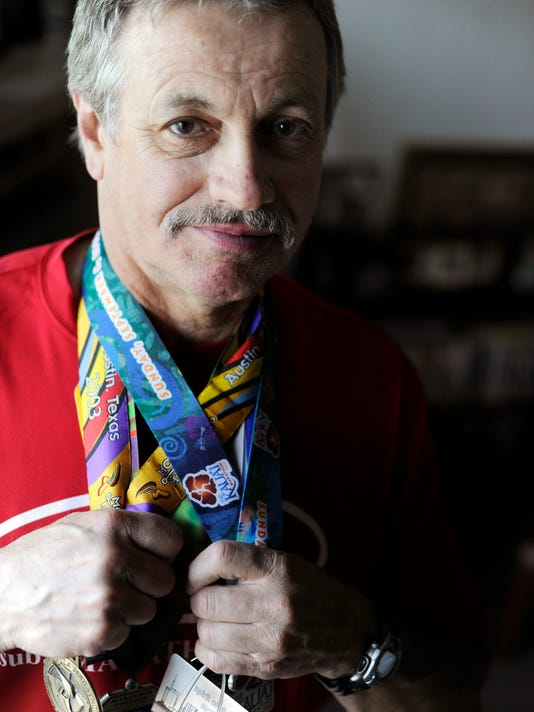 Clay Shaw poses with some of his many marathon medals in 2012. Shaw, now 62, recently completed his 184th and 185th marathons in his quest for 200. He also has scheduled a marathon in Alaska, which would be his 50th state -- for a second time.
