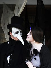 Joy Walker and Jennifer Southerington, dressed as an undertaker and Lenore from an Edgar Allen Poe poem, prepare the porch for trick-or-treaters in Staunton.