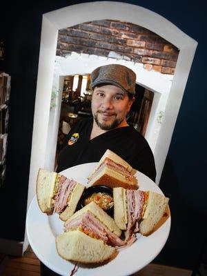 Mudgie's owner Greg Mudge with a muffaletta made of salami, mortadella, ham, ghiridinara, olives, provolone and mozzarella.
