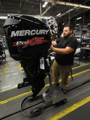 A worker places finishing touches on an engine at Mercury