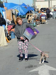 A resident moves what she can carry during a sweep of homeless encampments in Salinas on Thursday, March 24th in the Market Way area of Chinatown.