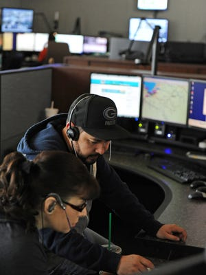 Dispatchers Sergio Ramirez and Lisa Perez work out a problem at Monterey County Emergency Communications in Salinas.