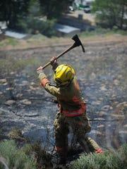 A firefighter chops a sagebrush after small fire broke