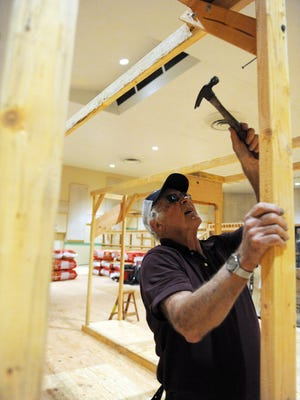 Volunteer Bob Rice works on a wooden frame that will display doors for sale at the Monterey County Habitat for Humanity ReStore at Fort Ord.
