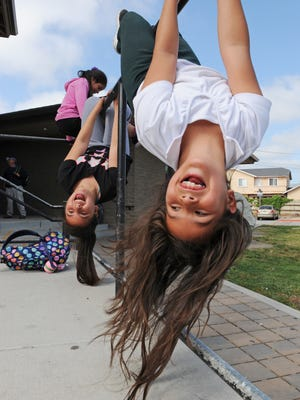 Stephanie Duran, 8, and friends play after school in front of the CŽésar Ch‡ávez Library in east Salinas.