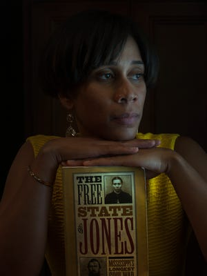 """Lawnside woman Eunice Smith poses for a photo with the book """"The Free State of Jones"""" in Lawnside Tuesday. Smith is a fourth-generation descendant of Newton Knight, Matthew McConaughey's title character in the movie """"Free State of Jones."""" The movie, which opens Friday, is about the establishment of one of the first mixed-race communities in America. Smith has a small role in the film."""