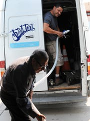 Alberto Garcia helps mobile detailer Eddie Ramirez fill up his truck with pure water from Aqualight in east Salinas.