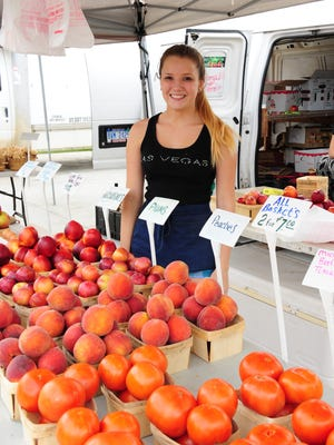 Shawnee Ransom helps her grandfather at the Westland Farmers and Artisans Market. DeWoulf Farms from Howell sells produce at the weekly event.