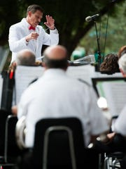 Harris Lanzel conducts the band during an event put