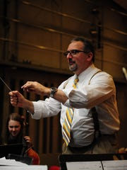 Retired orchestra teacher Bill Milicevic warms up area high school students before they perform Saturday at North Farmington High School at the Day for Strings event.