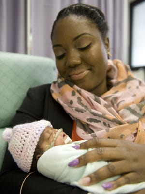 """Lavalle Thomas holds her daughter, Love Leak, who was born three months premature at Our Lady of Lourdes Medical Center in Camden in this file photo from 2013. Thomas was among the new mothers who received breastfeeding support from Lourdes, thanks to its efforts over the past five years to earn designation as a """"Baby Friendly"""" hospital."""