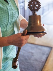 Gallagher holds a Rotary Club bell used to call meetings to order.