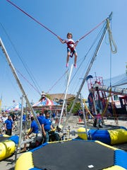 Seven year-old Hayley Hovey from Cairo, Ky. goes high in the air on the Bungee Jump ride at the Tri-Fest in Henderson, Ky., Saturday afternoon, April 16, 2016.