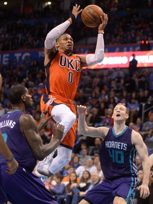 USA; Oklahoma City Thunder guard Russell Westbrook (0) drives to the basket between Charlotte Hornets forward Marvin Williams (2) and Charlotte Hornets center Cody Zeller (40) during the fourth quarter at Chesapeake Energy Arena.