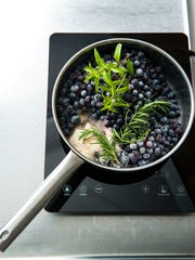 A pot of berries simmers with herbs before the canning process.