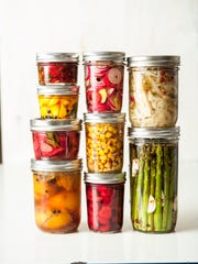 A selection of preserved vegetables in Mason jars.
