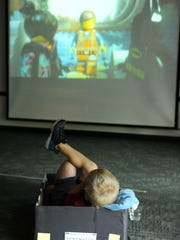 """Eljjah Snyder, 4, relaxes in a homemade cardboard car while at a drive-in showing of the """"Lego Movie"""" at the Evansville Vanderburgh Public Library's Oaklyn Branch  during a celebration of a prevous year's summer reading program. Elijah and his brother Joseph Snyder, 6, participated in many of the library's summer reading events and enjoyed reading over their break. The cars were made by several teen library volunteers who helped make the idea of a drive in more real to help local children celebrate the end of the library's summer reading program."""