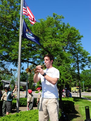 "Harrison High School senior Ben Fernquist plays ""Taps"" as the flag is raised by local scouts at the Memorial Day Ceremony held in downtown Farmington."