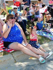 Denise Pattison and granddaughter Macy Tessoff wave as the Fourth of July Parade goes down Main Street in Milford.