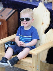 Two-year old Jordan Campbell of Farmington Hills takes a much-needed rest during Northville's Heritage Festival.