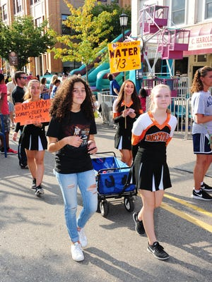 Northville High School Pom Pon members (front) Anisa Lahbiki, Vivian Landaw, and (back) Georgia Bernwanger and Victoria Nigoghosian take to the streets of downtown Northville selling cider, donuts and bottled water at this year's Heritage Festival.