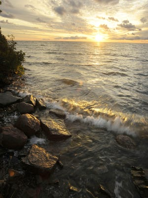 Sunrise over Lake Huron in the tip of the Thumb at Eagle Bay; waves wash over rocks on the shore at Grindstone City and the beach at Port Crescent State Park on Saginaw Bay.