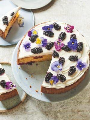 This pound cake is topped with a Greek yogurt-based topping, fresh berries and edible flowers.