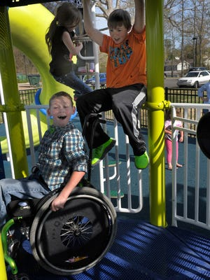 Cayden, left, and Conner Long play at an accessible playground that was dedicated to them in their hometown of White House.